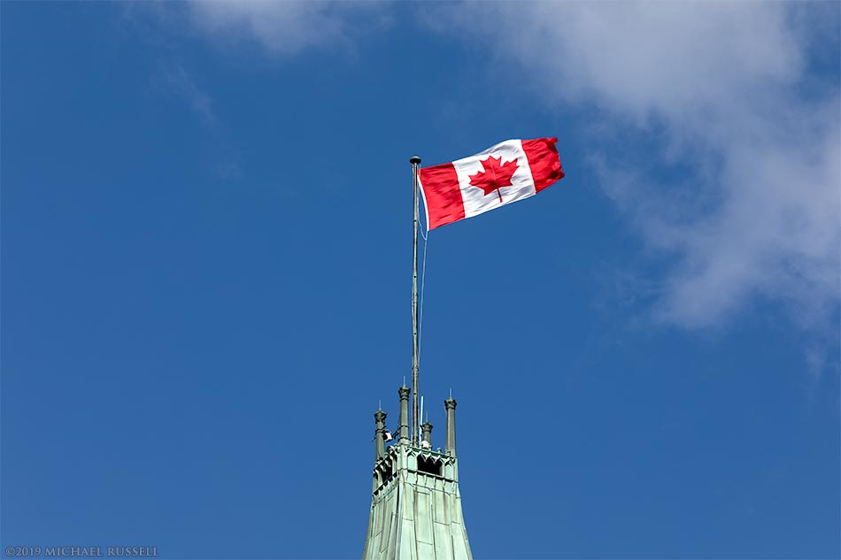 canadian flag on peace tower at parliament buildings in ottawa canada