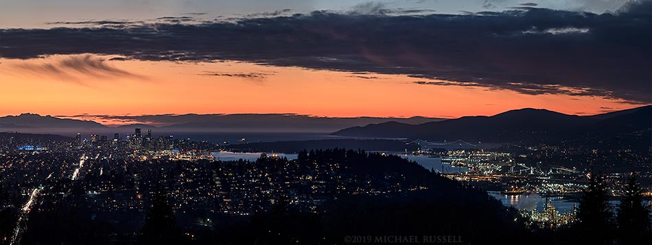 view of the city of vancouver after sunset from above